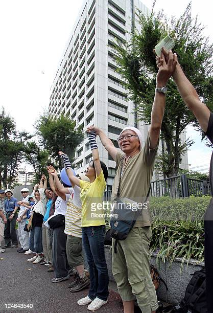 Protesters link their hands to form a human chain around the Ministry of Economy Trade and Industry building during a rally against nuclear energy in...