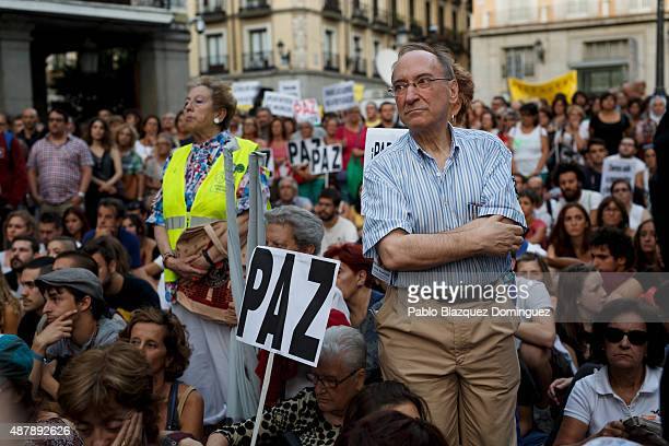 Protesters listen a speech as a placard reads 'Peace' during a demonstration to show solidarity and support for refugees on September 12 2015 in...