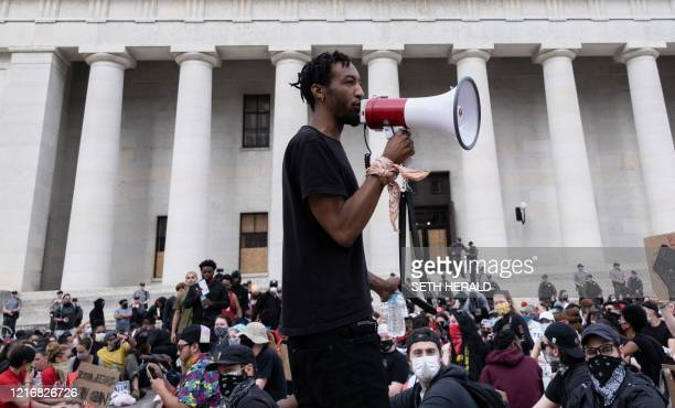 Protesters listen to a man speak as they gather peacefully in front of the Ohio Statehouse in Downtown Columbus, Ohio June 1, 2020 to protest the...