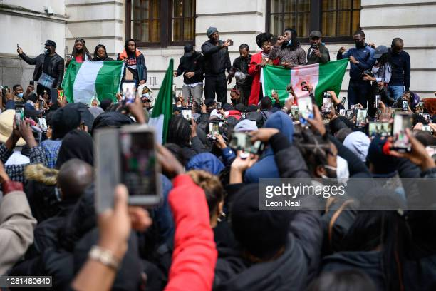 Protesters listen to a speech calling for the end of police killings of the public in Nigeria, during a demonstration on October 21, 2020 in London,...
