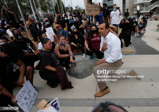 Protesters listen to San Jose Mayor Sam Liccardo as he takes a knee during a protest of the killing of George Floyd outside of San Jose City Hall in...
