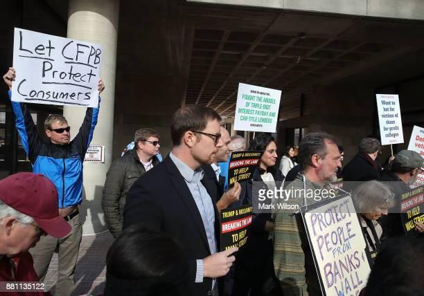 Protesters listen to Sen Elizabeth Warren speak in front of the Consumer Financial Protection Bureau headquarters on November 28 2017 in Washington...