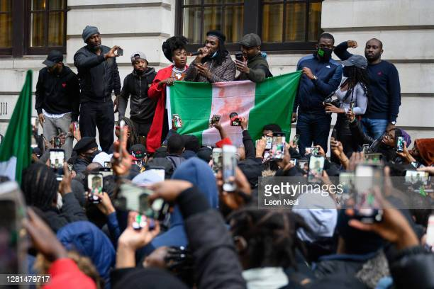 Protesters listen to speech calling for the end of police killings of the public in Nigeria, during a demonstration on October 21, 2020 in London,...