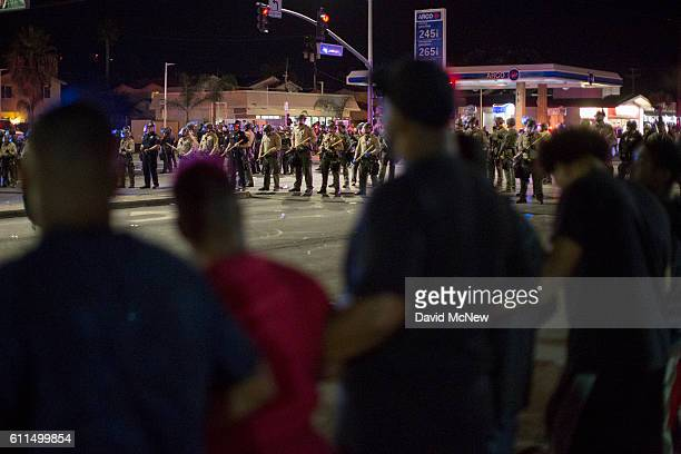 Protesters lock arms as officers amass after an unlawful assembly is declared near the site where an unarmed black man Alfred Olango had been shot by...