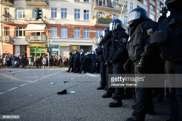 Protesters look on as riot police stand guard during the 'Welcome to Hell' protest march on July 6 2017 in Hamburg Germany Leaders of the G20 group...