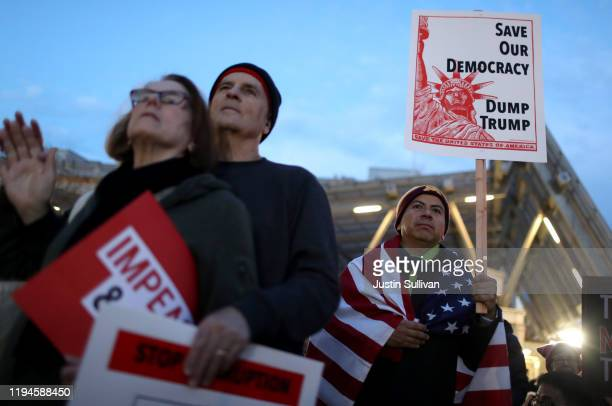 Protesters look on during a demonstration urging congress to impeach US President Donald Trump on December 17 2019 in San Francisco California The...