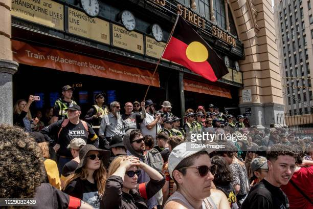 Protesters look on while gathering at the Flinders Street Railway Station during the demonstration. Thousands of people have hit the streets of...