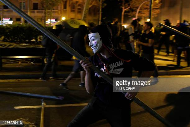 Protesters make barricades during a demonstration called by the local Republic Defence Committees in Barcelona on October 16 after police arrested 51...