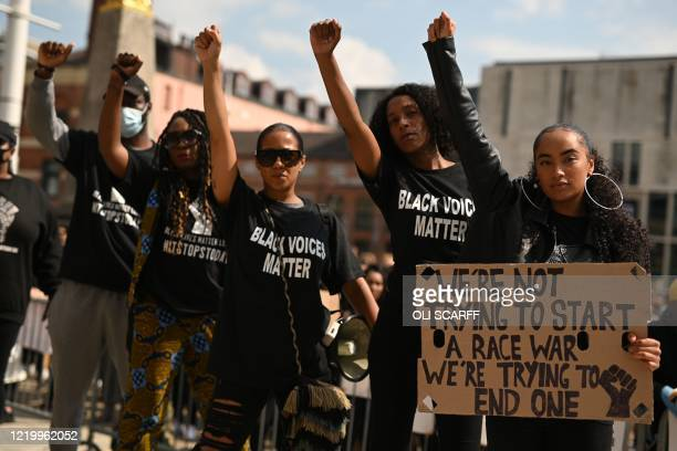 Protesters make Black Lives Matter fists at a gathering in support of the Black Lives Matter and Black Voices Matter movements in Leeds in northern...