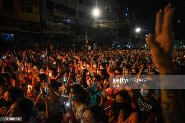 Protesters make the three-finger salute during a candlelight vigil to honour those who have died during demonstrations against the military coup in...