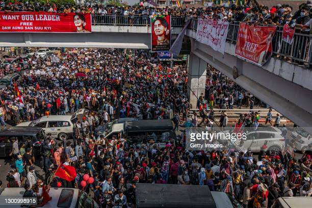Protesters make three-finger salutes and hold up banners and posters as they march on February 08, 2021 in downtown Yangon, Myanmar. Tens of...