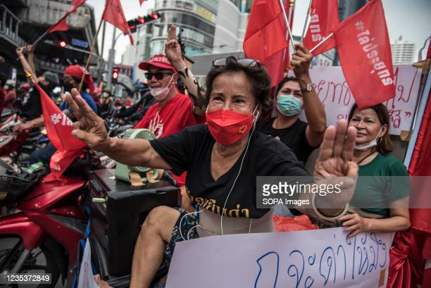 Protesters make three-finger salutes while holding flags during the car mob rally. Anti-government protesters gathered at Asok intersection before...