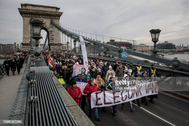 Protesters march across Budapest's famous Szechenyi Chain Bridge with a sign saying We Have Had Enough during a demonstration against recent...