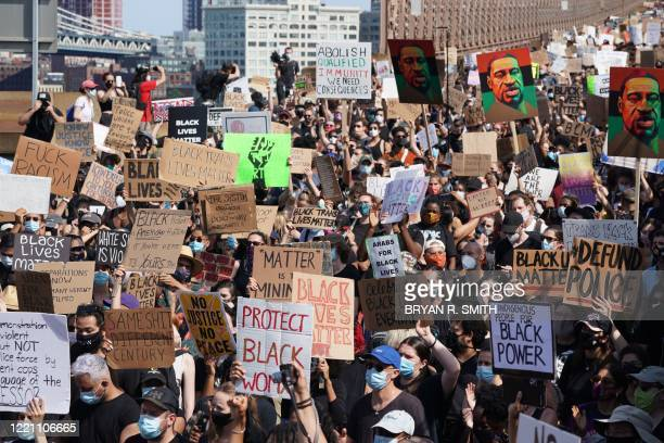 Protesters march across the Brooklyn Bridge over the death of George Floyd by Minneapolis Police on June 19, 2020 in New York. - The US marks the end...