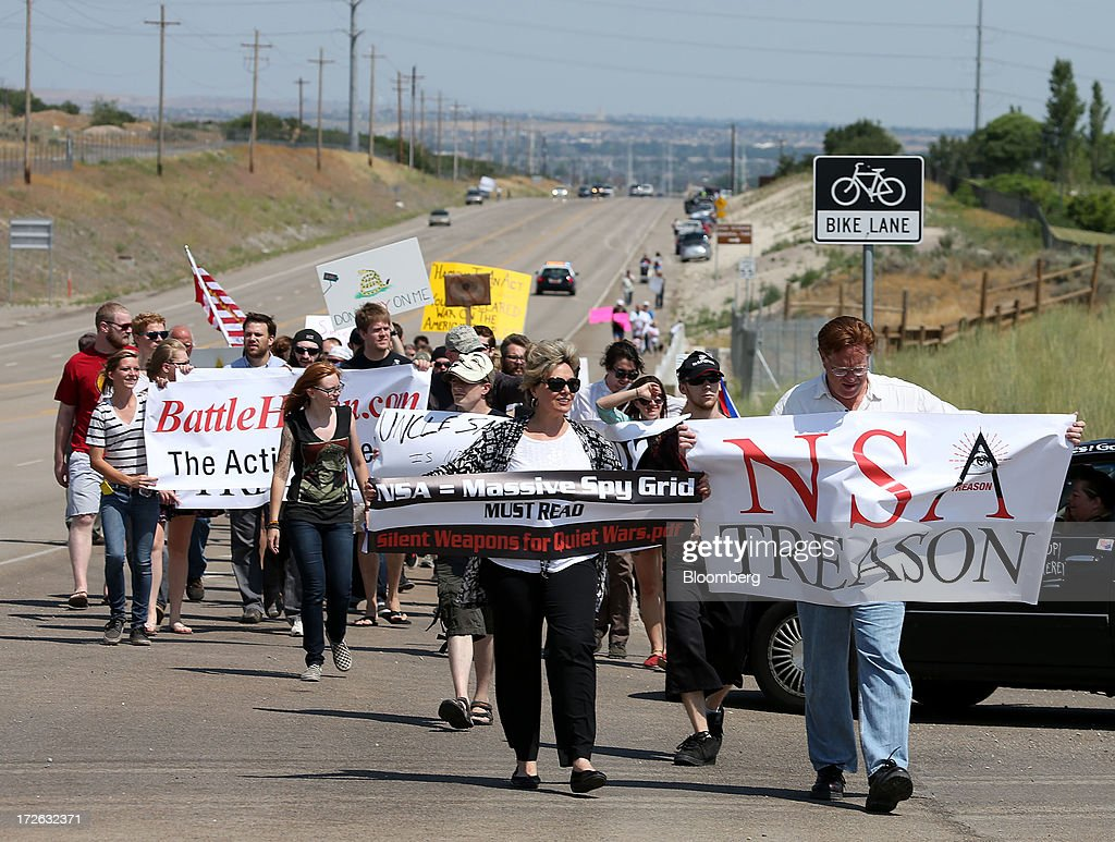 Protesters march along the roadside to the new National Security Agency (NSA) Utah Data Center being built in Bluffdale, Utah, U.S., on Thursday, July 4, 2013. Russian President Vladimir Putin said NSA whistleblower Edward Snowden must quit hurting American interests if he wants to remain in Russia, after an official said the fugitive applied for asylum there. Photographer: George Frey/Bloomberg via Getty Images