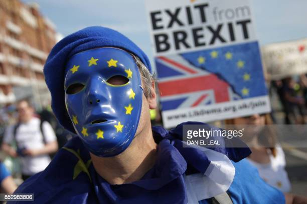 Protesters march along the seafront holding placards and waving European and Union flags in Brighton on September 24 on a march against Brexit...