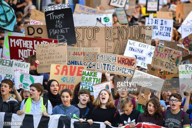 Protesters march and hold placards as they attend the Global Climate Strike on September 20 2019 in Edinburgh Scotland Millions of people are taking...