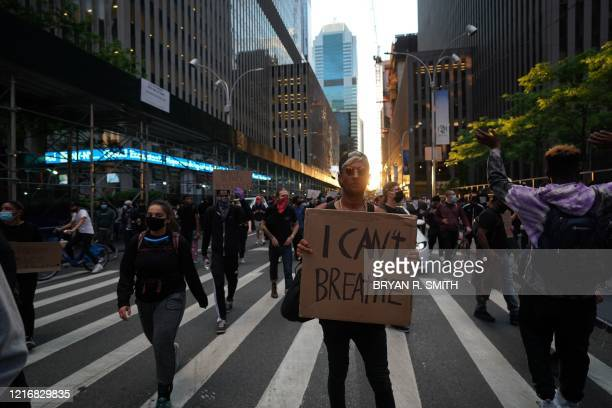 Protesters march and hold placards during demonstrations over the death of George Floyd by a Minneapolis police officer on June 1 2020 in New York...