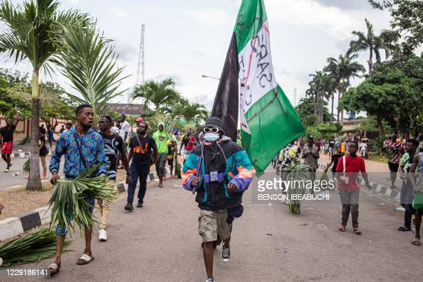 Protesters march at Alausa, the Lagos State Secretariat, in Lagos on October 20 after the Governor of Lagos State, Sanwo Olu, declared 24-hour curfew...