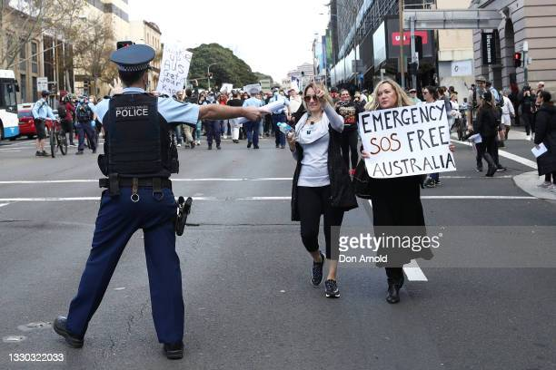Protesters march down George St on July 24, 2021 in Sydney, Australia. Anti-lockdown and anti-vaccination activists gathered in cities across...