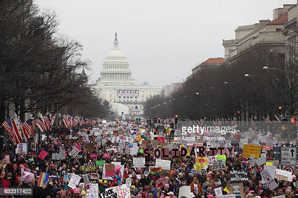 Protesters march down Pennsylvania avenue during the Women's March on Washington January 21 2017 in Washington DC The march is expected to draw...