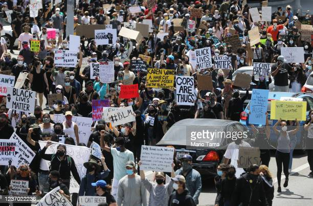 protesters march during a demonstration organized by Black Lives Matter following the death of George Floyd on May 30 2020 in Los Angeles California...
