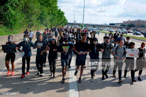 Protesters march during a demonstration over the death of George Floyd a black man who died after a white policeman kneeled on his neck for several...