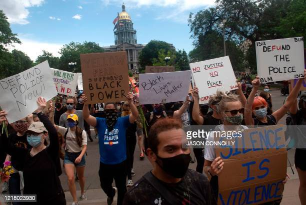 Protesters march during a demonstration over the death of George Floyd in Denver, Colorado on June 6, 2020. - Demonstrations are being held across...