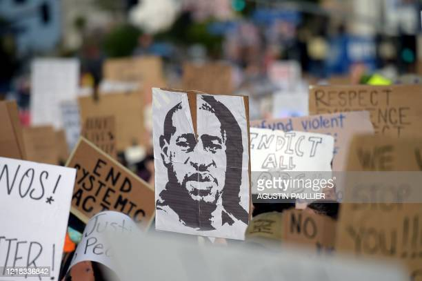 TOPSHOT Protesters march holding placards and a portrait of George Floyd during a demonstration against racism and police brutality in Hollywood...