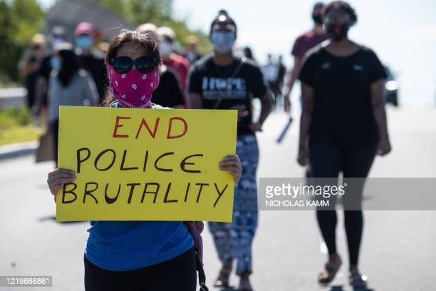 Protesters march in Bridgewater, New Jersey, on June 13, 2020 during a demonstration against police brutality and racism following the death of...