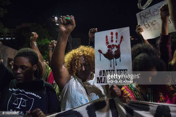 Protesters march in Charlotte, North Carolina, on September 23, 2016 following the shooting of Keith Lamont Scott by police three days earlier and...