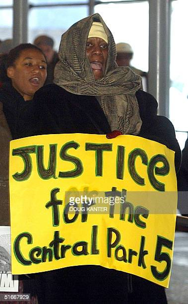 Protesters march in front of a city court in New York 05 December 2002 over five men charged with the 1989 sexual assault on a jogger in Central Park...