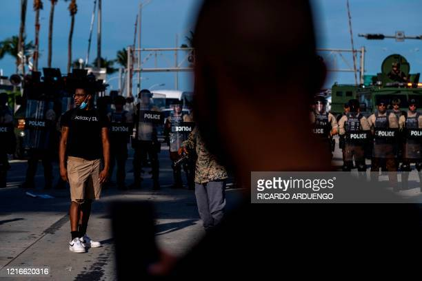 Protesters march near a row of Miami police officers and an armored vehicle during a rally in response to the recent death of George Floyd an unarmed...