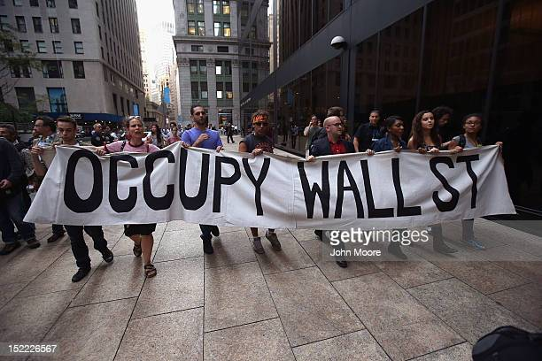 Protesters march near the New York Stock Exchange during a demonstration marking the one-year anniversary of the Occupy Wall Street movement on...
