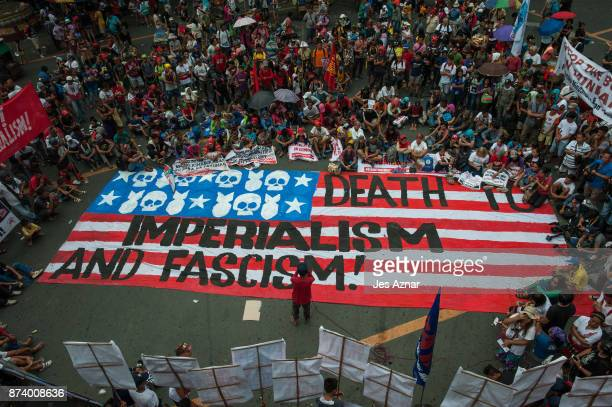 Protesters march on the streets and carry a US flag to burn as protest to US President Trump's visit in the Philippines on November 14 2017 in Manila...