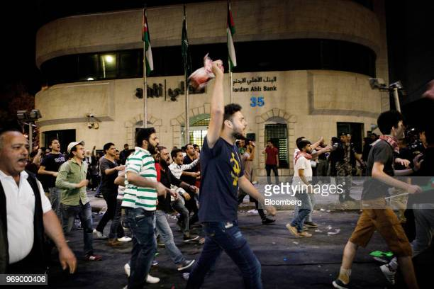 Protesters march past a Jordan Ahli Bank branch towards anti riot police during a demonstration against a draft income tax law near the prime...