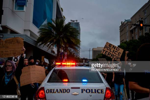 Protesters march past a police car during a rally in response to the recent death of George Floyd in police custody in Minneapolis, in Orlando,...