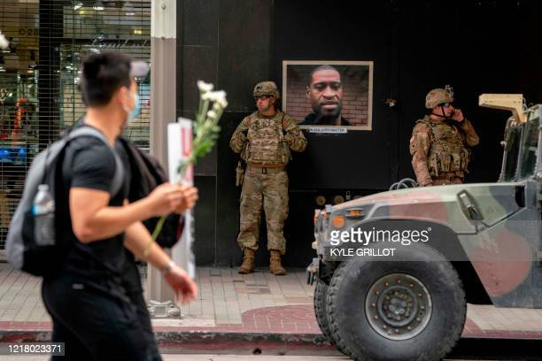 TOPSHOT Protesters march past California National Guard soldiers standing near a portrait of George Floyd during a demonstration over the death of...