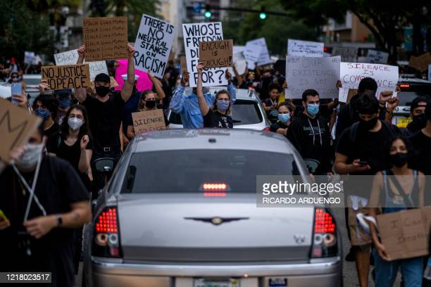 Protesters march past cars during a rally in response to the recent death of George Floyd in police custody in Minneapolis, in Orlando, Florida on...