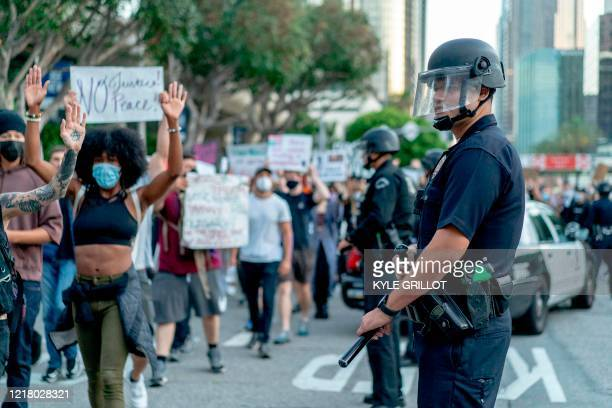 Protesters march past LAPD officers during a demonstration over the death of George Floyd while in Minneapolis Police custody, in downtown Los...