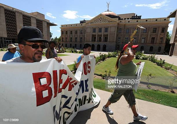 Protesters march past the Arizona State Capital Building as they campaign against the controversial state law SB1070 which criminalizes illegal...