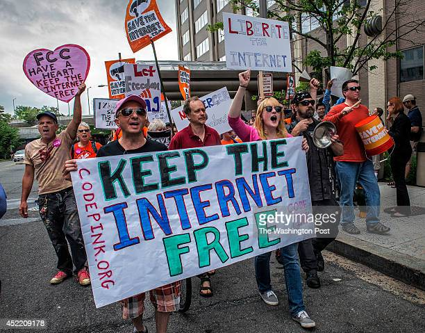 Protesters march past the FCC headquarters before the Commission meeting on net neutrality proposal on May 2014 in Washington DC