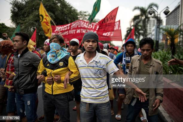 Protesters march the streets of Manila a day ahead of US President Trump's arrival on November 11 2017 in Manila Philippines Hundreds of Filipinos...
