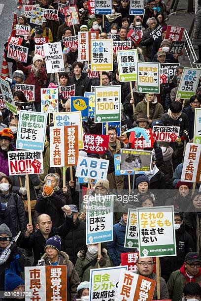 Protesters march the streets of Shibuya holding placards to protest against Japanese Prime Minister Shinzo Abe during a protest denouncing his...