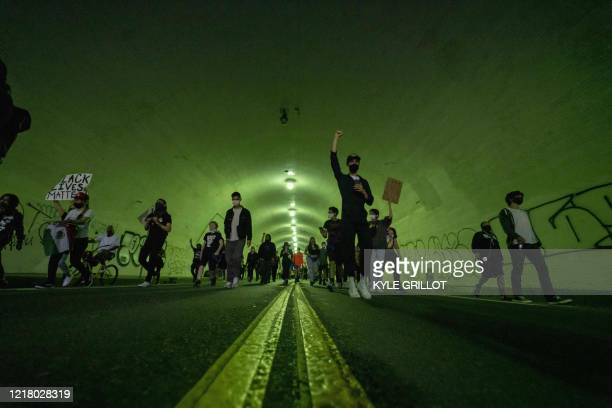 TOPSHOT Protesters march through the 2nd Street tunnel during a demonstration over the death of George Floyd while in Minneapolis Police custody in...