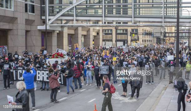 Protesters march through the city during a silent march in memory of George Floyd a day before jury selection for the trial of former Minneapolis...