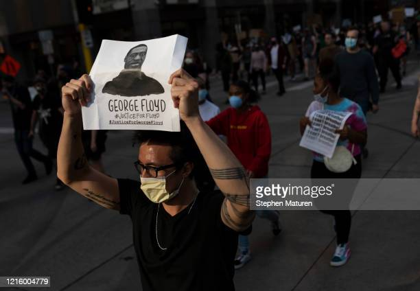 Protesters march through the street on May 28, 2020 in downtown Minneapolis, Minnesota. Police and protesters continued to clash for a third night...