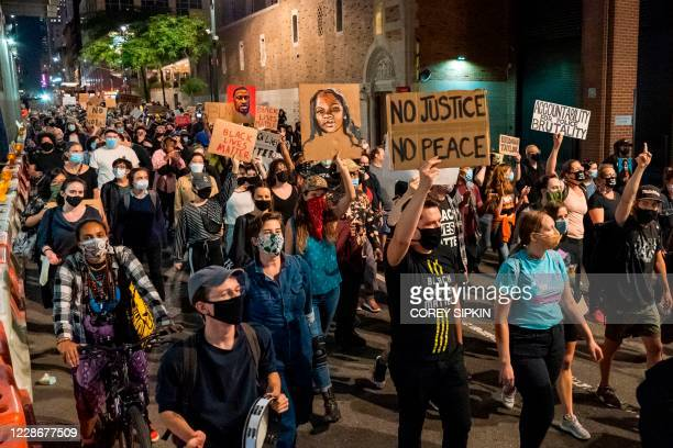 Protesters march through the streets after a judge announced the charges brought by a grand jury against Detective Brett Hankison, one of three...