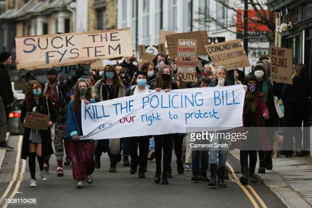 """Protesters march through the streets during a """"Kill The Bill"""" protest on March 20, 2021 in Truro, England. Protests are taking place across the..."""