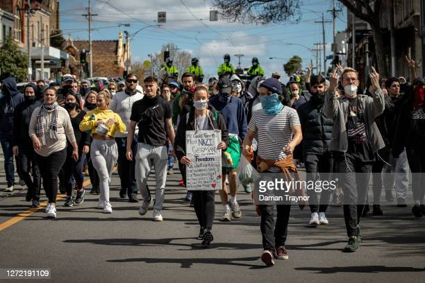 """Protesters march through the streets of the city on September 13, 2020 in Melbourne, Australia. Anti-lockdown protesters organised a """"freedom walk""""..."""
